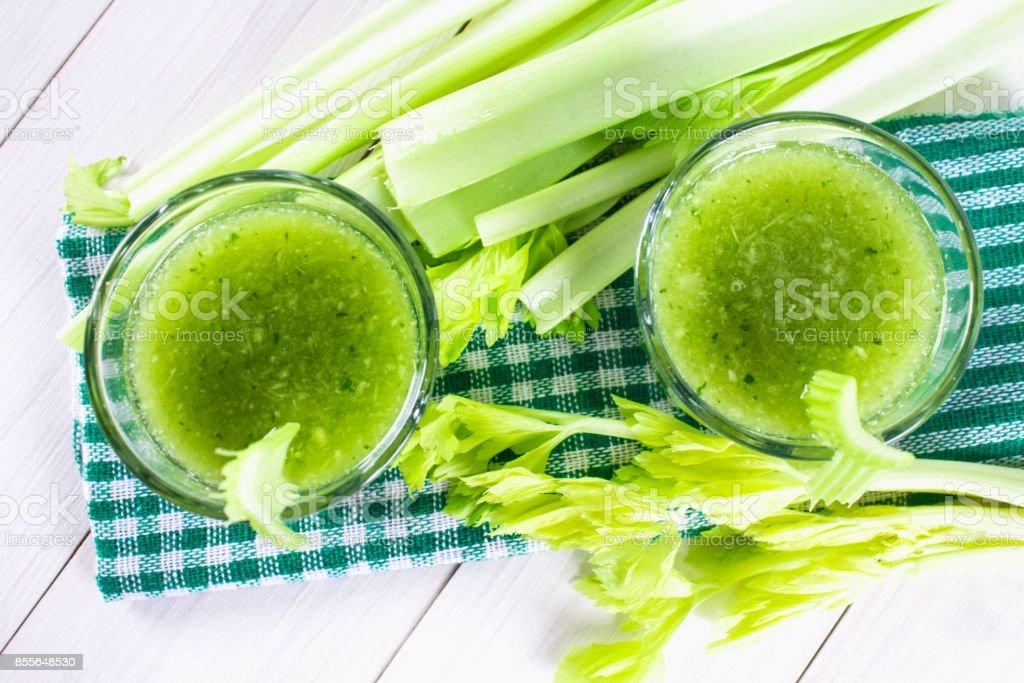 Cóctel vegetal de apio hojas, estilo de vida saludable en un fondo blanco de madera. - foto de stock