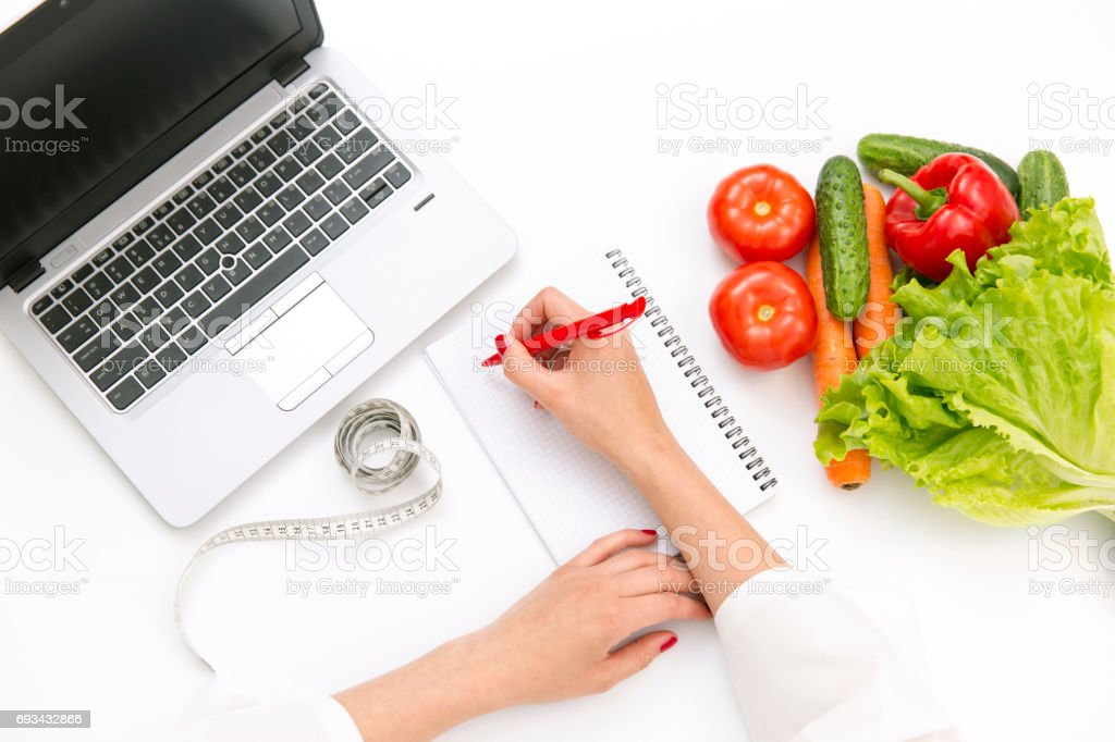 Vegetable diet nutrition or medicaments concept. Doctors hands writing diet plan, ripe vegetable composition, laptop and measuring tape on white background stock photo