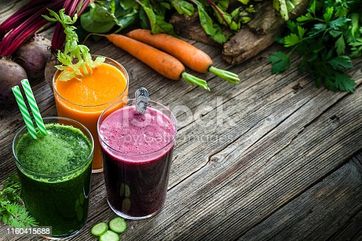 Vegetable drinks: high angle view of three drinking glasses filled with beet, carrot and green vegetables juice shot on rustic wooden kitchen table. Vegetables like beet, carrots, cucumber, broccoli, avocado and celery are all around the juice glasses. The composition is at the left of an horizontal frame leaving a useful copy space for text and/or logo at the right. Predominant colors are purple, green and orange. Low key DSRL studio photo taken with Canon EOS 5D Mk II and Canon EF 100mm f/2.8L Macro IS USM.