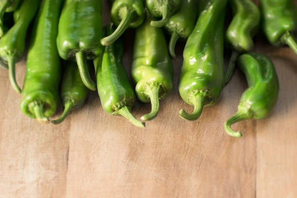 vegetable ingredients. green peppers on a wooden background - green chilli pepper stock photos and pictures