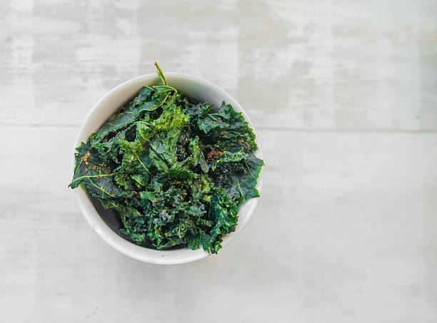 Vegetable Kale Chips Green veggie chips or crisps on white bowl that are prepared using vegetables kale stock pictures, royalty-free photos & images