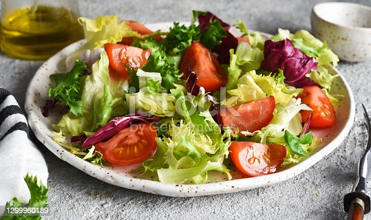 Vegetable mix salad with tomatoes and sauce on a concrete background.