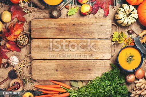 Healthy food cooking background. Vegetable ingredients and homemade soup. Fresh garden carrots, onions, pumpkins, ginger and spices on rustic wooden background, top view, copy space