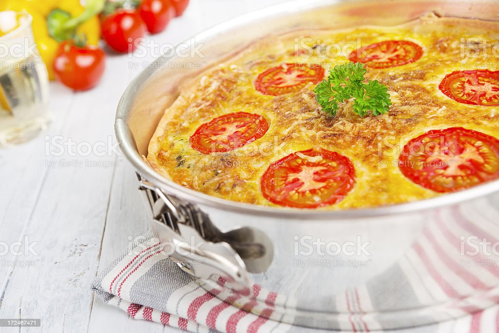 Vegetable quiche on a bright, rustic table royalty-free stock photo