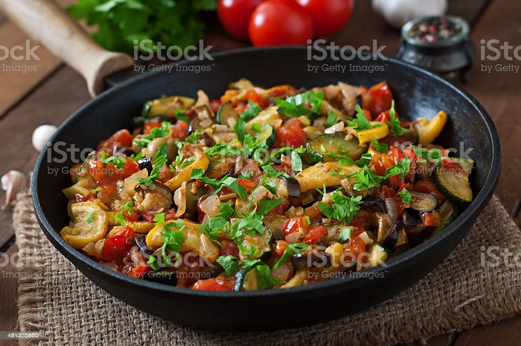 Vegetable Ratatouille in frying pan on a wooden table stock photo