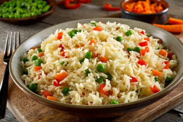 Vegetable Rice Pilaf Delicious vegetable rice pilaf with green peas, carrots and red peppers. basmati rice stock pictures, royalty-free photos & images