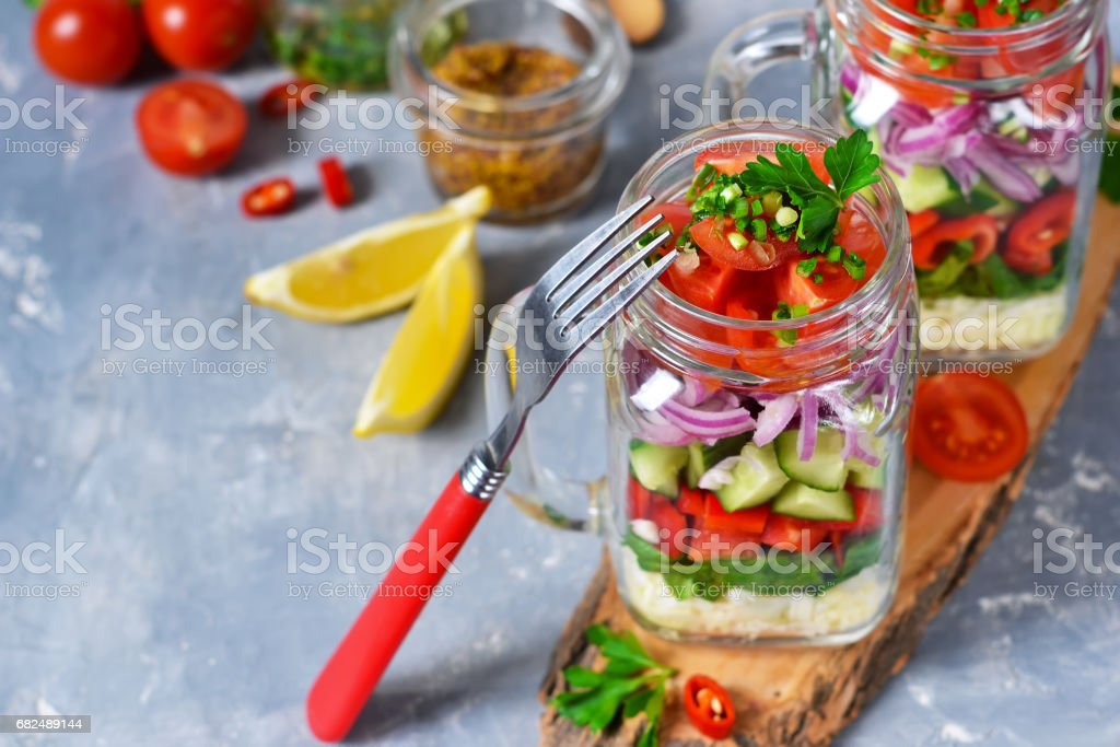 Vegetable salad in a glass jar with sauce on a concrete background royalty-free stock photo