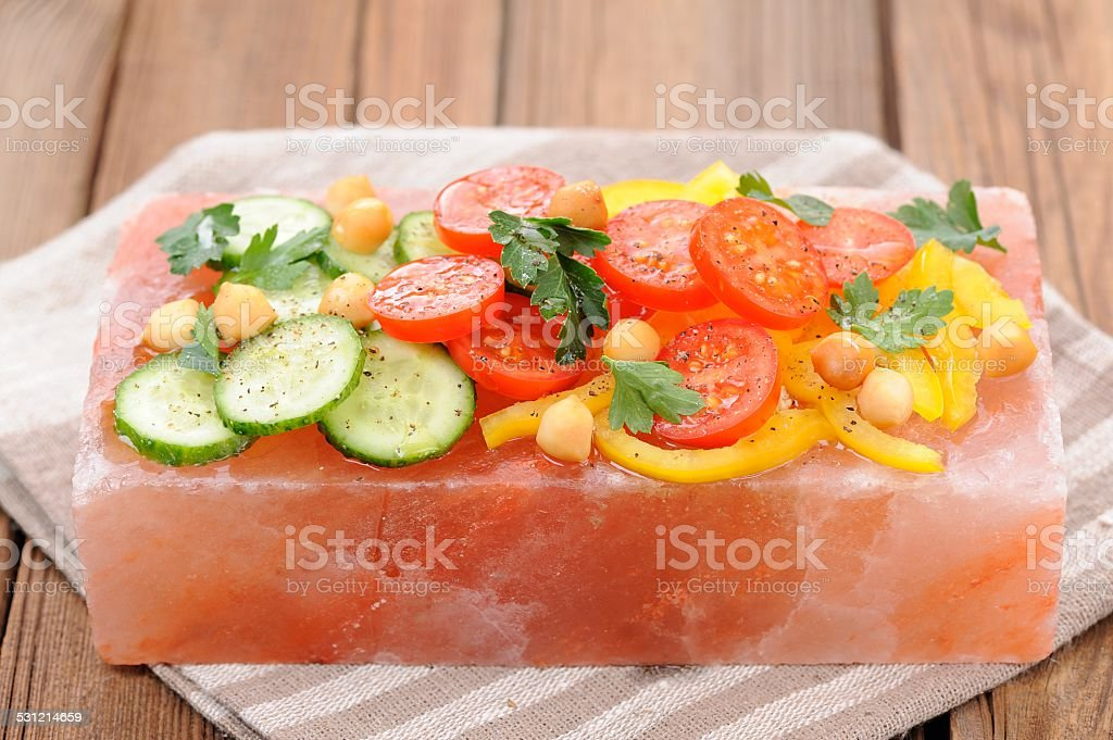 Vegetable salad on pink salt block on stripe napkin stock photo
