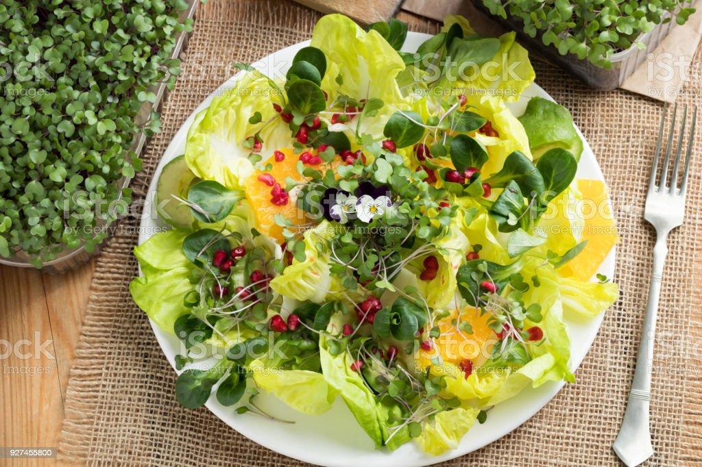 Vegetable salad with fresh kale and broccoli microgreens, lettuce, corn salad, pomegranate, orange, avocado and edibe flowers stock photo
