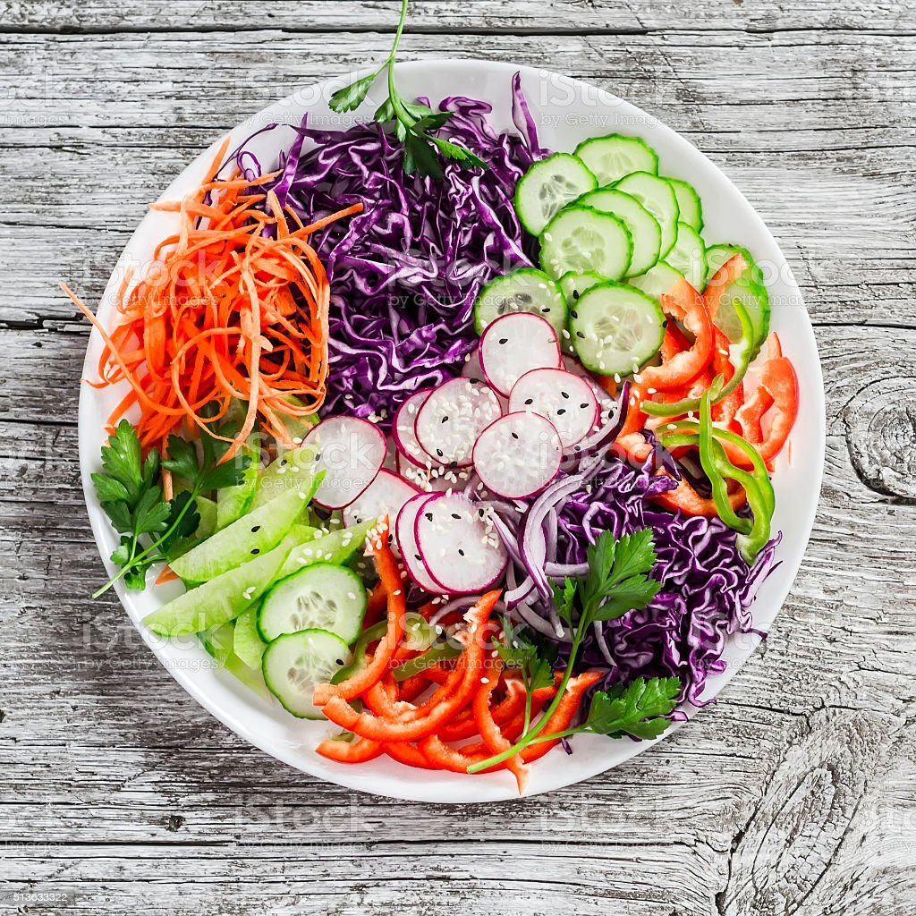 vegetable salad with red cabbage, cucumber, radish, carrots, sweet peppers stock photo