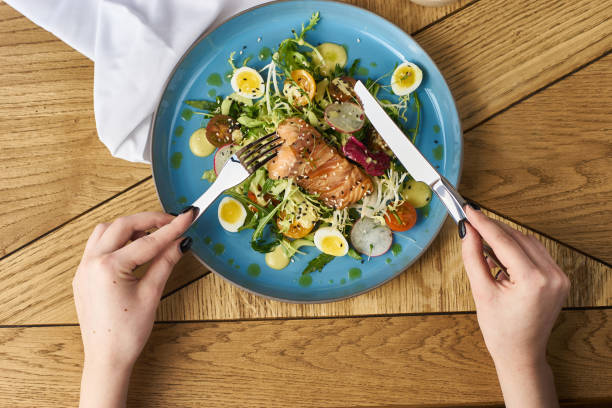 vegetable salad with salmon - woman eating salmon imagens e fotografias de stock