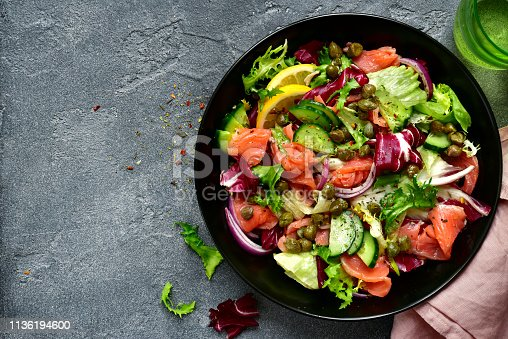 Vegetable salad with salted salmon in a black bowl over slate, stone or concrete background.Top view with copy space.