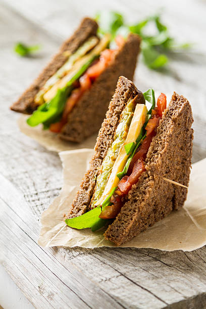 vegetable sandwich with zucchini burger, cheese, ruccola and tomatoes - sandwich stockfoto's en -beelden
