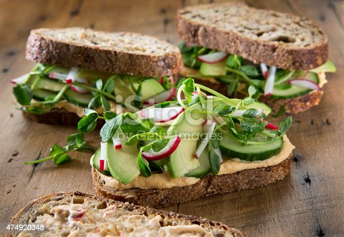 Three healthy vegetarian sandwich's on a rustic wood background. Sandwich's are on multigrain bread with roasted red pepper hummus , radish's ,cucumber , pea shoots and avocado.