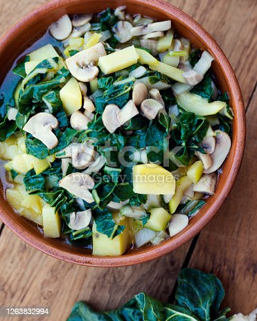 Homemade vegetable soup with chard on wooden background