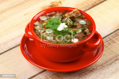 Delicious Vegetable Soup with Smoked Pork Ribs, Cabbage, Leek, Carrot, Garlic Greens and Sour Cream in Red Bowl isolated on Wooden background