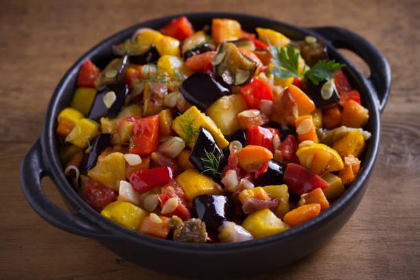 Guiso de verduras: berenjenas, pimentón, tomates, calabacín, zanahorias y cebollas. Ensalada de verduras estofadas - foto de stock