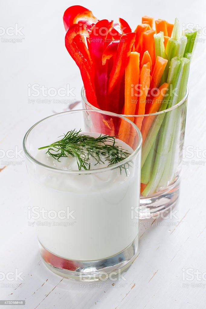 Vegetable sticks (pepper, celery, carrot) in glass and yogurt stock photo