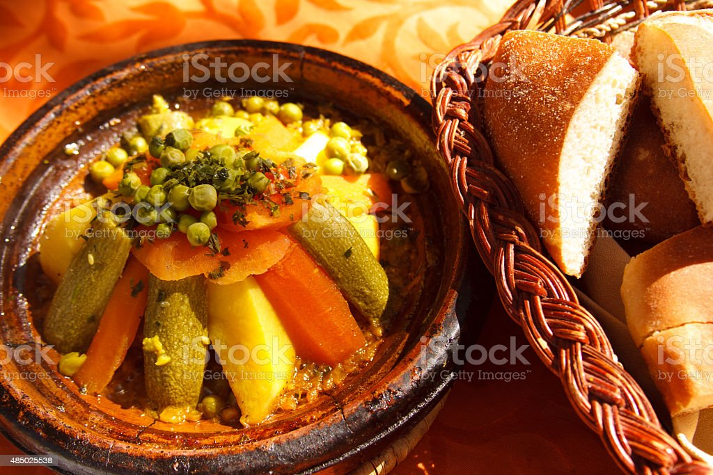 Vegetable Tagine on Worn Clay Plate, Bread Basket, Morocco stock photo