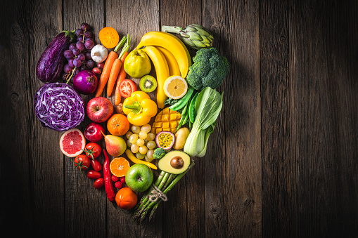 Vegetables and fruit with heart shape as concept of cardiovascular health on wooden rustic table