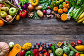 Vegetables and fruits vegan food assorted arrangement varied leaving rustic wood copy space background