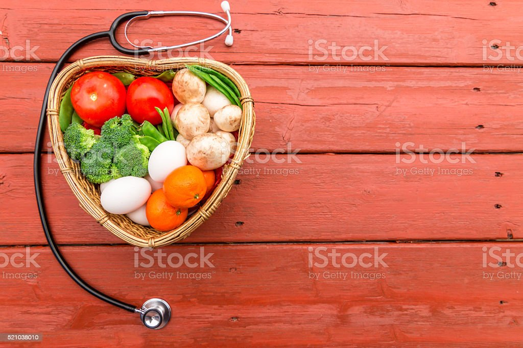 vegetables and furits in a heart shape basket with  stetho stock photo