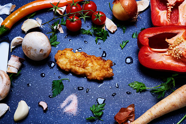 gemüse und schnitzel auf schneidebrett - paprikaschnitzel stock-fotos und bilder