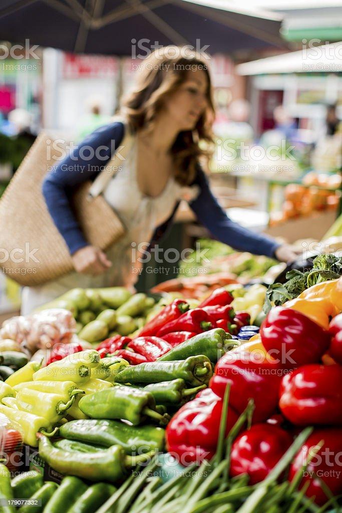 Verduras en un mercado con mujer joven - foto de stock
