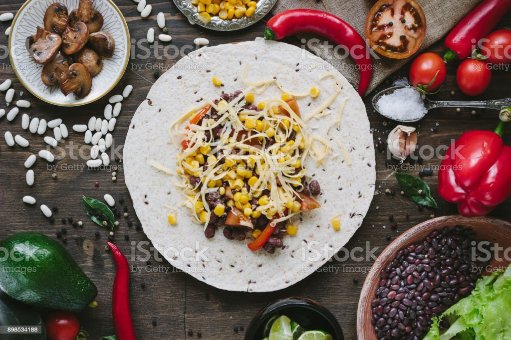 Vegetables, beans and cheese over tortilla bread - vegetarian mexican salad tacos. stock photo