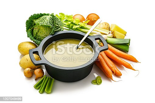 High angle view of a black cooking pan filled with a healthy vegetables broth isolated on white background. Fresh multi colored vegetables like carrots, kale, potatoes, celery and onions are all around the pan. High resolution 42Mp studio digital capture taken with Sony A7rii and Sony FE 90mm f2.8 macro G OSS lens