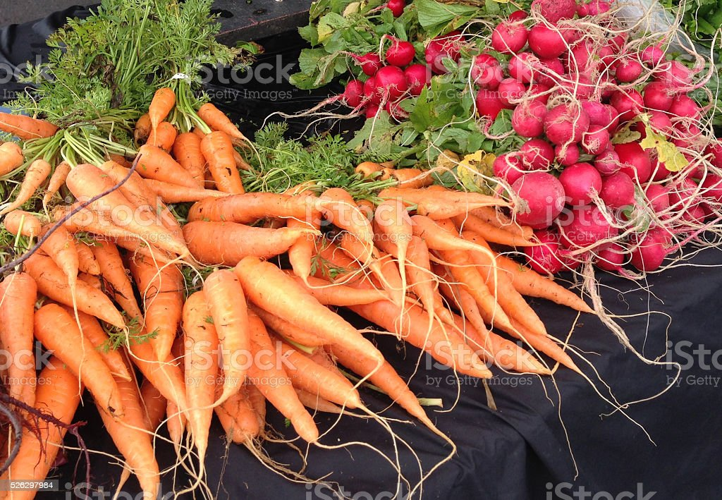 Vegetables, carrots and radishes at a farmers market stock photo