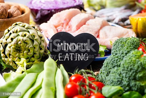 a black heart-shaped signboard with the text mindful eating, on a pile of different vegetables, such as French beans, cherry tomatoes, a head of broccoli, and some pieces of chicken in the background