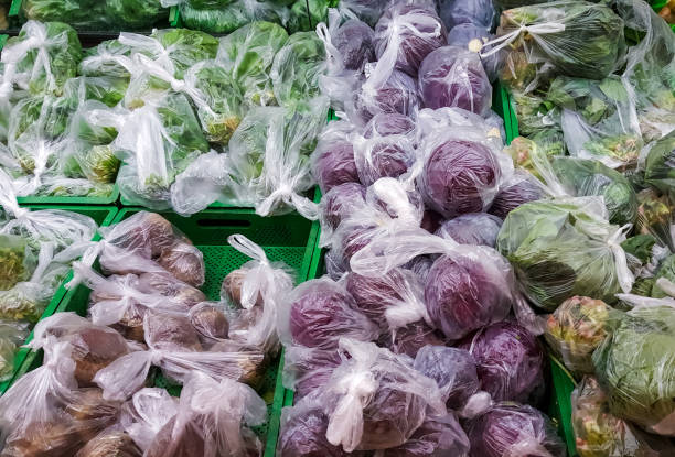Vegetables displayed in shopping bags to prevent coronavirus spread on supermarket racks stock photo