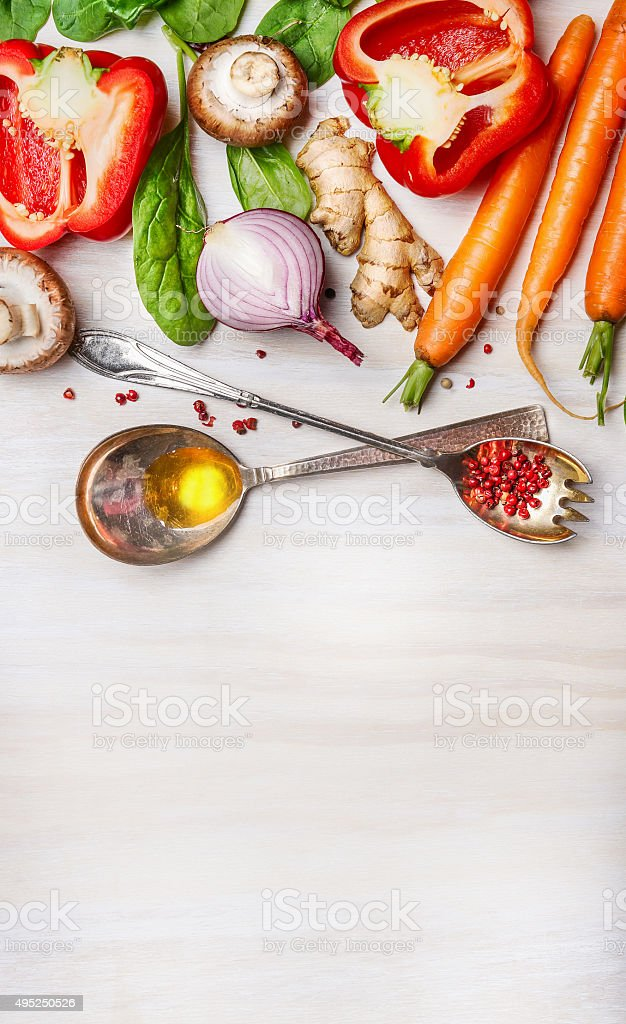 Vegetables for Healthy cooking with spoons on light background stock photo