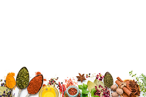 Cooking and seasoning backgrounds: Top view of multi colored vegetables, herbs and spices placed side by side at the bottom of a white background leaving useful copy space for text and/or logo. The composition includes rosemary, parsley, star anise, curry powder, bay leaves, nutmeg, salt, pepper, chili pepper, cinnamon sticks, dried orange slices, olive oil and dried oregano High key DSRL studio photo taken with Canon EOS 5D Mk II and Canon EF 100mm f/2.8L Macro IS USM.