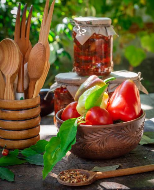 gemüse in einen braunen ton teller und gläser mit konserven auberginen - peperoni stiche stock-fotos und bilder