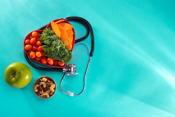 Vegetables in a heart bowl and nuts with Stethescope  on a blue background stock photo