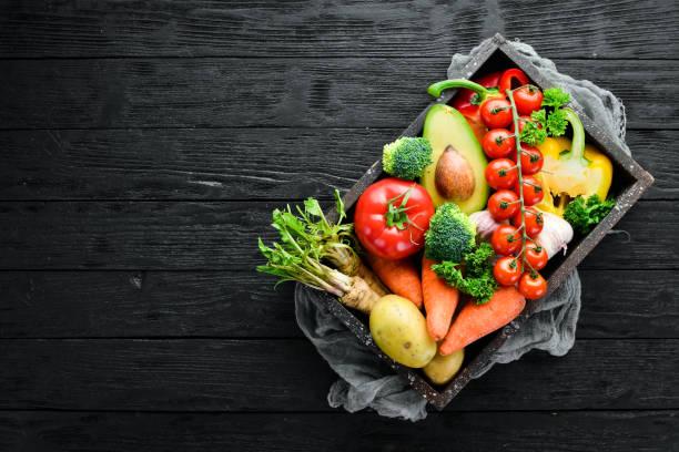 Vegetais em uma caixa de madeira. Abacate, pepino, cebola, alho, tomates, cenouras, rábano. Vista superior. Espaço livre para o seu texto. - foto de acervo