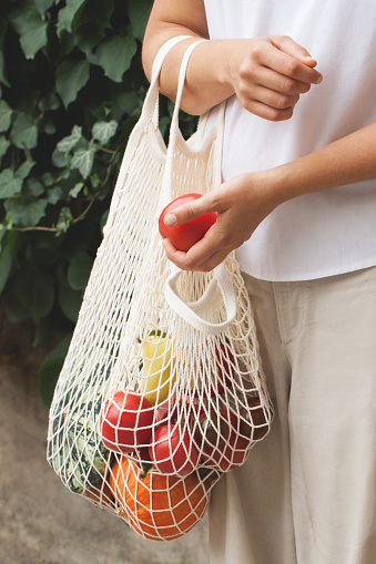 istock Vegetables in an eco bag and girl's hands 1166856824