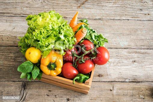 istock Vegetables in basket on wooden table 658506092