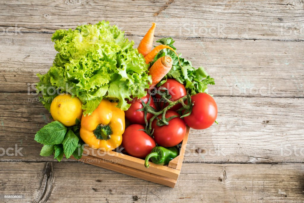 Vegetables in basket on wooden table stock photo