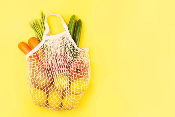 Gemüse in Stoff-Einkaufstasche auf gelbem Hintergrund. – Foto