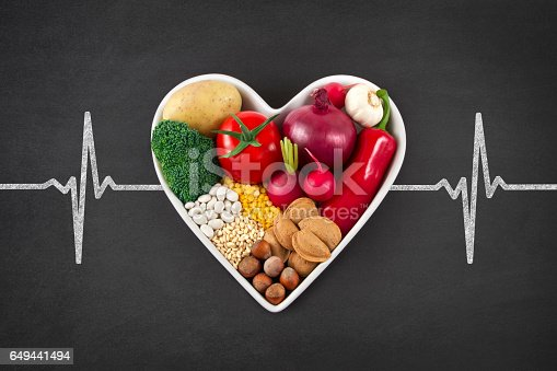 Heart health concept with related foods in white heart shaped bowl. potato red peppers, broccoli, radish, red onion, garlic, dry beans, almonds, nuts, and other legumes were arranged in heart shape plate on blackboard with drawing of pulse trace.