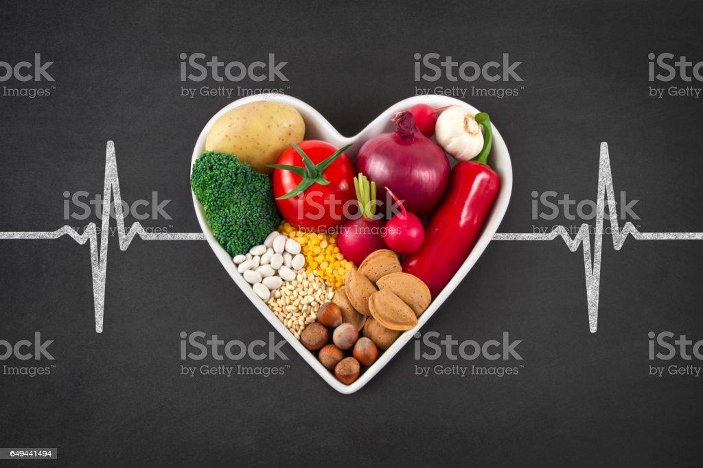 Verduras en el recipiente en forma de corazón en pizarra - foto de stock