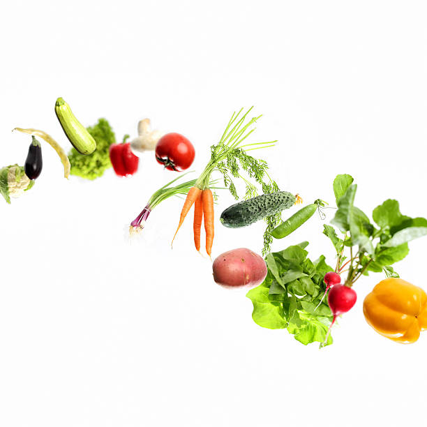 vegetables in motion Falling or flying vegetables , selective focus. The veggies fall from the left of image to the bottom right in an elegant curve. The selective focus technique give more realism to the movement and a 3D effect. medium group of objects stock pictures, royalty-free photos & images