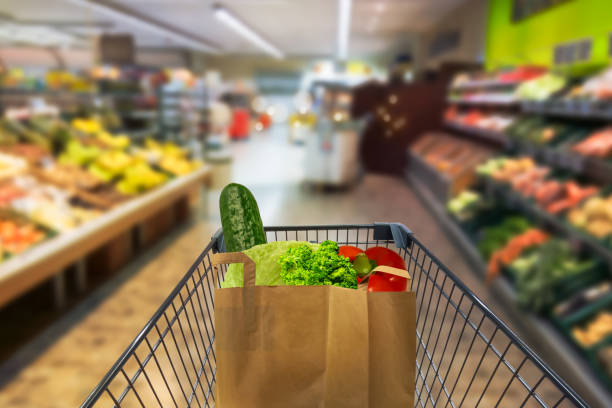 vegetables in paper bag in shopping cart vegetables in paper bag in shopping cart produce aisle stock pictures, royalty-free photos & images