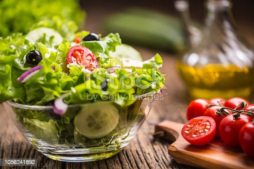 879977192 istock photo Vegetables lettuce salad with tomatoes onion cheese and olives. 1056241892