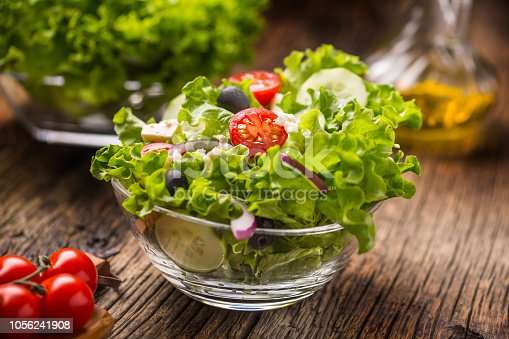 879977192 istock photo Vegetables lettuce salad with tomatoes onion cheese and olives. 1056241908