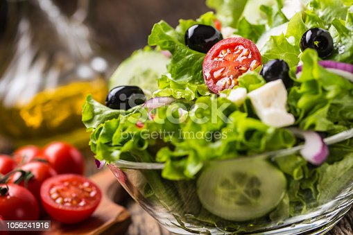 879977192 istock photo Vegetables lettuce salad with tomatoes onion cheese and olives. 1056241916