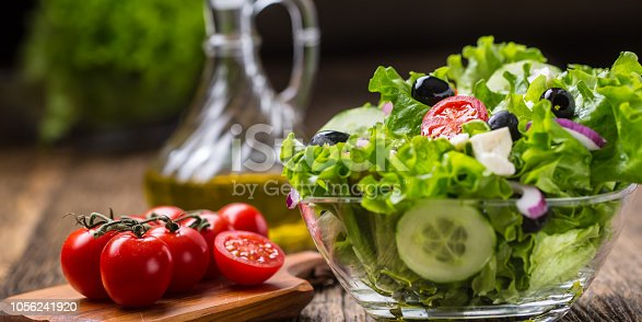 879977192 istock photo Vegetables lettuce salad with tomatoes onion cheese and olives. 1056241920